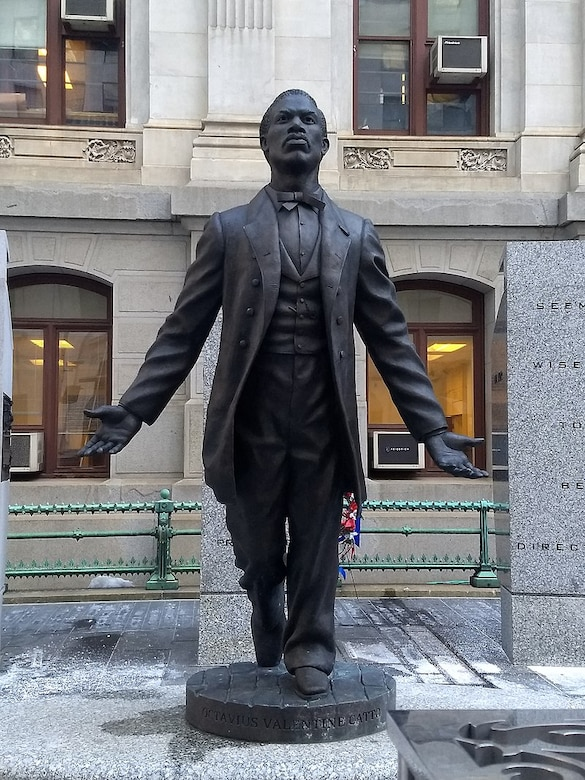 A statue shows a man leaning forward with his arms outstretched.