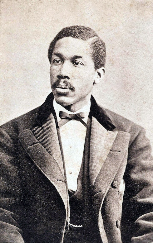 In a photo from the 1800s, a man dressed in a suit poses for the camera.
