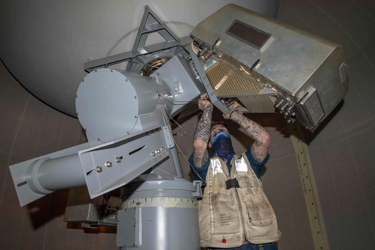 A man works on a satellite dish console.