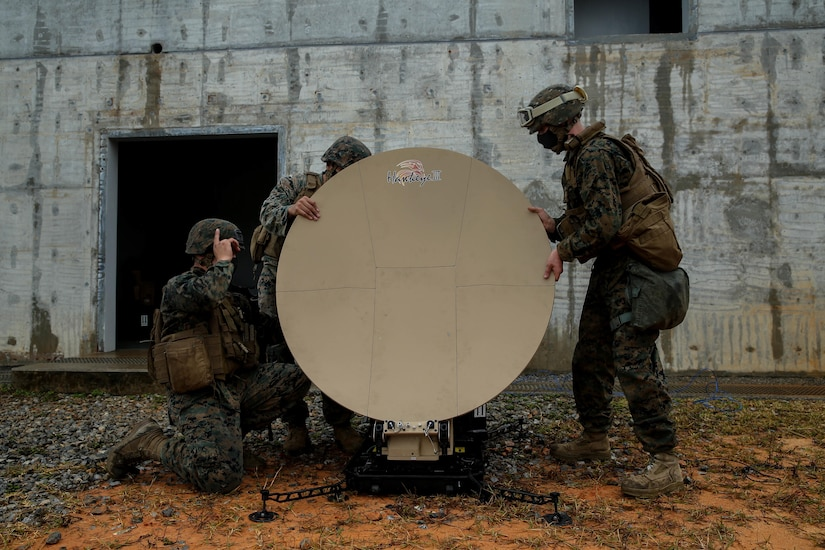 Three Marines set up a satellite dish.