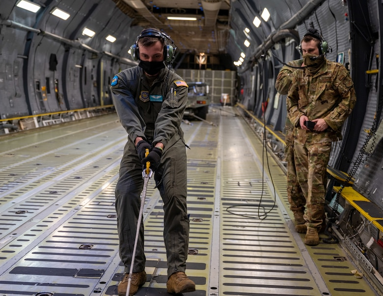 """Airman 1st Class Kody Roundtree, 9th Airlift Squadron loadmaster, reels in a winch on a C-5M Super Galaxy before a flight at Dover Air Force Base, Delaware, Jan. 19, 2021.The 9th AS, also known as the """"Proud Pelicans,"""" routinely flies local training missions to maintain operational readiness in support of the nation's outsized global airlift capability. (U.S. Air Force photo by Airman 1st Class Faith Schaefer)"""