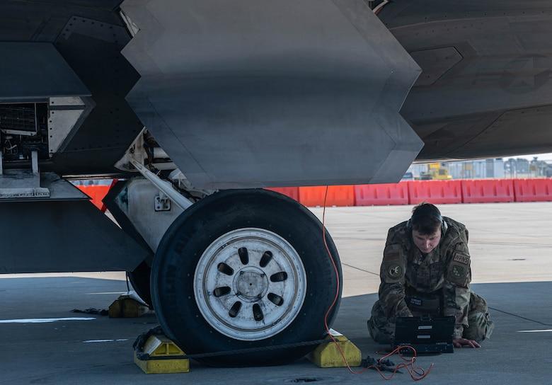 An Airman inspects computer data from an aircraft.