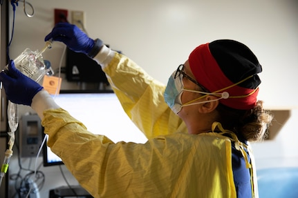 A nurse wearing personal protective equipment prepares intravenous medication for a patient.