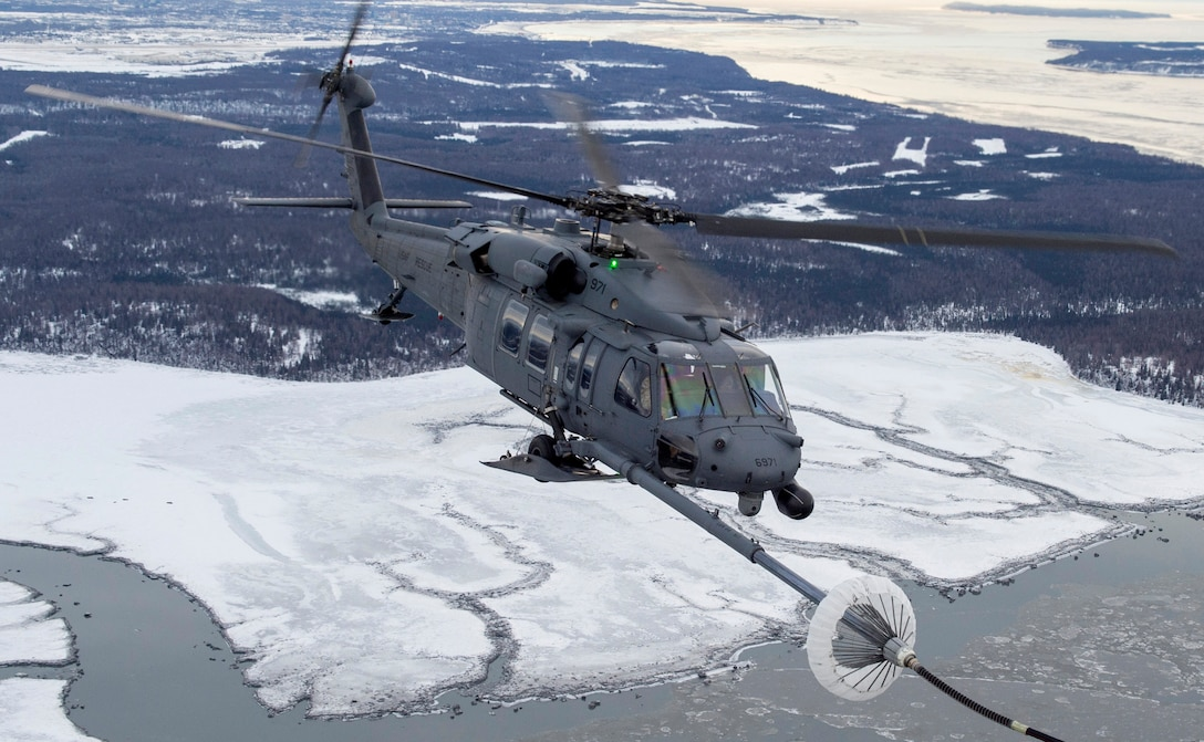 A U.S Air Force HH-60G Pave Hawk helicopter assigned to the 210th Rescue Squadron, Alaska Air National Guard, conducts aerial refueling from a U.S. Air Force HC-130J Combat King II assigned to the 211th Rescue Squadron, Alaska Air National Guard, over Alaska, Jan. 21, 2021, during Operation Noble Defender. Operation Noble Defender is a North American Air Defense Command air-defense operation that allows dynamic training for operational readiness in an Arctic environment.