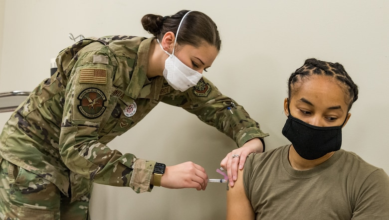 Tech. Sgt. Tiana White, 436th Airlift Wing Tactics and Leadership Nexus cadre, receives the COVID-19 vaccine administered by Airman 1st Class Madelyn Renda, 436th Healthcare Operations Squadron medical technician, Jan. 22, 2021, at Dover Air Force Base, Delaware. White was among the first Team Dover members who voluntarily received the vaccine in accordance with Department of Defense guidance. The vaccine was granted emergency use authorization by the U.S. Food and Drug Administration for use in prevention of COVID-19. (U.S. Air Force photo by Roland Balik)