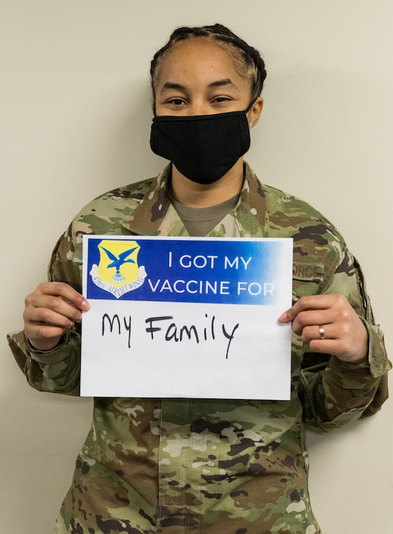 Tech. Sgt. Tiana White, 436th Airlift Wing Tactics and Leadership Nexus cadre, displays a sign stating why she volunteered for the COVID-19 vaccine Jan. 22, 2021, at Dover Air Force Base, Delaware. White was among the first Team Dover members who voluntarily received the vaccine in accordance with Department of Defense guidance. The vaccine was granted emergency use authorization by the U.S. Food and Drug Administration for use in prevention of COVID-19. (U.S. Air Force photo by Roland Balik)