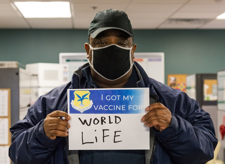 Henry Daniel, 436th Force Support Squadron material handler, displays a sign stating why he volunteered for the COVID-19 vaccine Jan. 22, 2021, at Dover Air Force Base, Delaware. Daniel was among the first Team Dover front-line workers who voluntarily received the vaccine in accordance with Department of Defense guidance. The vaccine was granted emergency use authorization by the U.S. Food and Drug Administration for use in prevention of COVID-19. (U.S. Air Force photo by Roland Balik)
