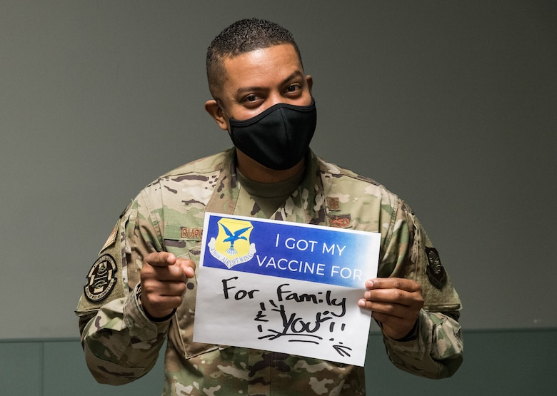 Master Sgt. Andrew Burgos, 436th Operational Medical Readiness Squadron mental health flight chief, displays a sign stating why he volunteered for the COVID-19 vaccine Jan. 20, 2021, at Dover Air Force Base, Delaware. Burgos was among the first Team Dover front-line workers who voluntarily received the vaccine in accordance with Department of Defense guidance. The vaccine was granted emergency use authorization by the U.S. Food and Drug Administration for use in prevention of COVID-19. (U.S. Air Force photo by Roland Balik)