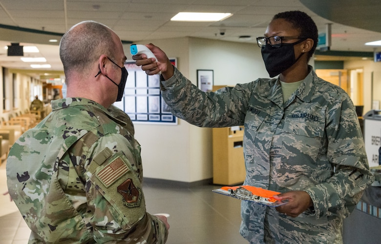 Chief Master Sgt. Jeremiah Grisham, 436th Airlift Wing interim command chief, has his temperature taken by Airman 1st Class Daija Norwood, 436th Operational Medical Readiness Squadron dental assistant, after entering the 436th Medical Group Clinic Jan. 20, 2021, at Dover Air Force Base, Delaware. Grisham was among the first Team Dover senior leaders who voluntarily received the COVID-19 vaccine in accordance with Department of Defense guidance. The vaccine was granted emergency use authorization by the U.S. Food and Drug Administration for use in prevention of COVID-19. (U.S. Air Force photo by Roland Balik)