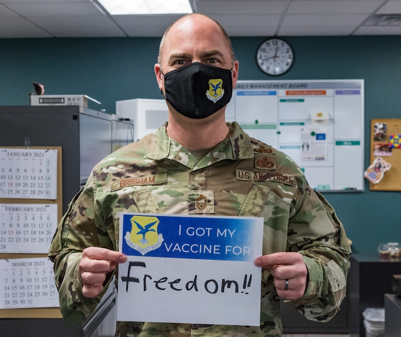 Chief Master Sgt. Jeremiah Grisham, 436th Airlift Wing interim command chief, displays a sign stating why he volunteered for the COVID-19 vaccine Jan. 22, 2021, at Dover Air Force Base, Delaware. Grisham was among the first Team Dover senior leaders who voluntarily received the vaccine in accordance with Department of Defense guidance. The vaccine was granted emergency use authorization by the U.S. Food and Drug Administration for use in prevention of COVID-19. (U.S. Air Force photo by Roland Balik)