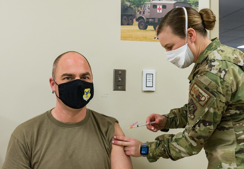 Chief Master Sgt. Jeremiah Grisham, 436th Airlift Wing interim command chief, receives the COVID-19 vaccine administered by Staff Sgt. Kelsey Loeser, 436th Medical Group unit training manager, Jan. 22, 2021, at Dover Air Force Base, Delaware. Grisham was among the first of Team Dover senior leaders who voluntarily received the vaccine in accordance with Department of Defense guidance. The vaccine was granted emergency use authorization by the U.S. Food and Drug Administration for use in prevention of COVID-19. (U.S. Air Force photo by Roland Balik)
