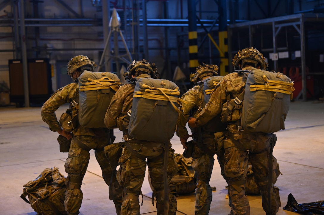U.S. Army paratroopers assigned to the 1st Squadron (Airborne), 91st Cavalry Regiment, 173rd Airborne Brigade, assigned to Grafenwoehr Training Area, Germany, conduct buddy-checks during a paratrooper briefing.
