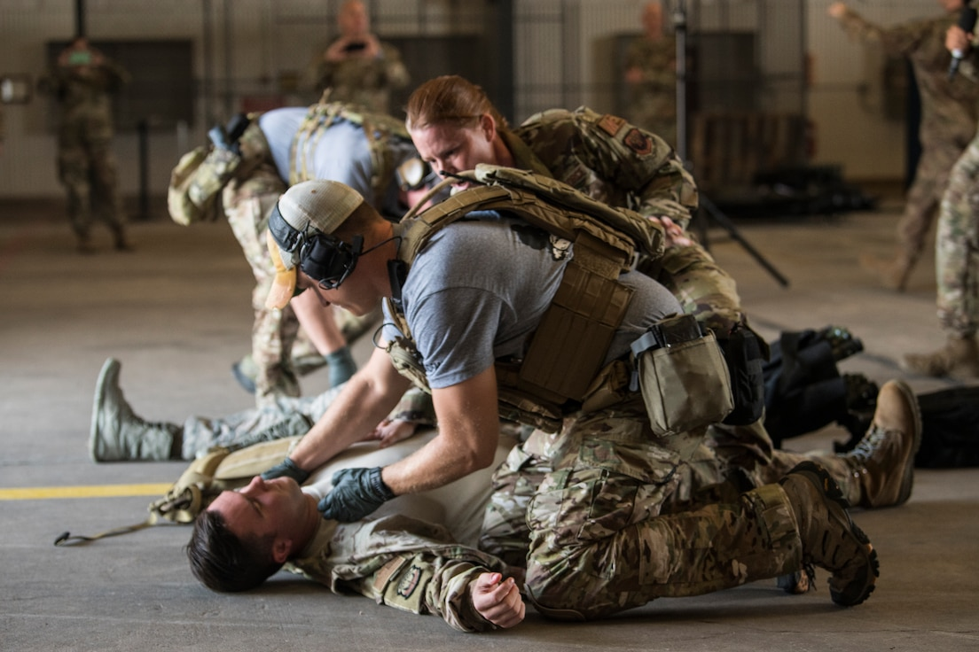 An Airman pretends to check for a pulse on another Airman simulating injuries