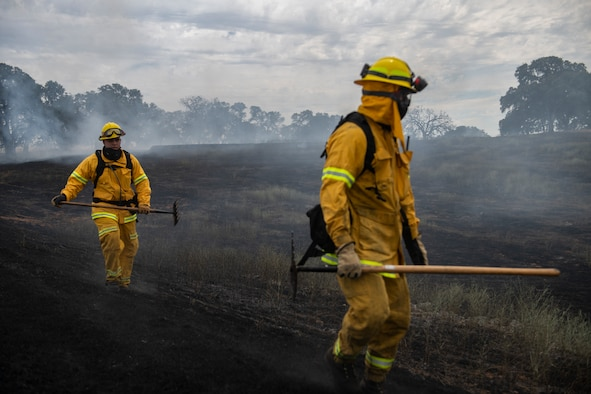 Two firefighters walk through a charred landscape holding axes.