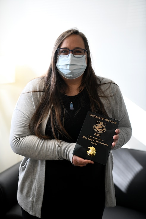 Amy Hernandez, the Director of Psychological Health at the 178th Wing, poses while holding the 178th Wing 2020 Civilian of the Year Award plaque.