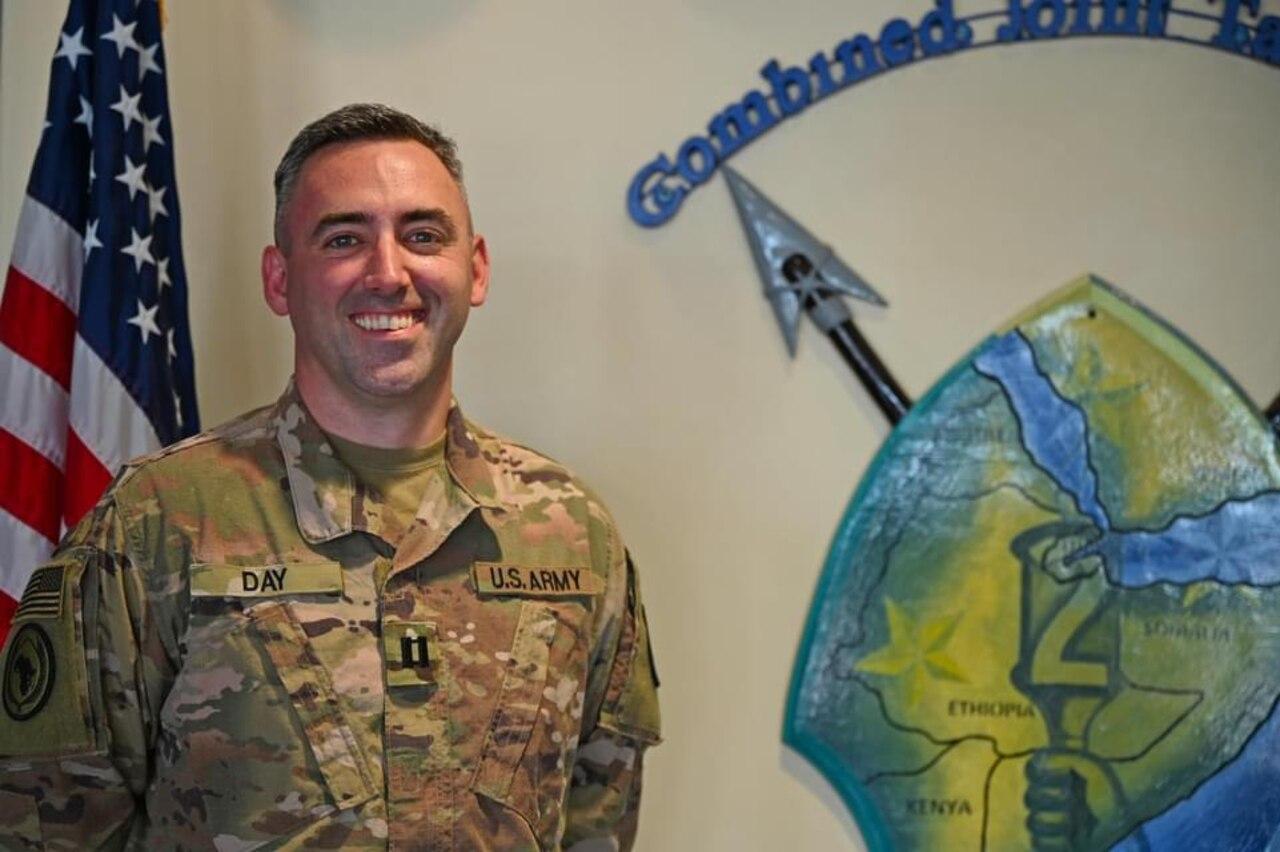 A man in combat uniform smiles beside a unit logo.