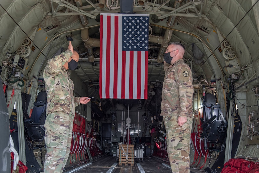 Two men facing each other hold up their right hands inside a C-130 airplane. A U.S. flag hangs in the background.