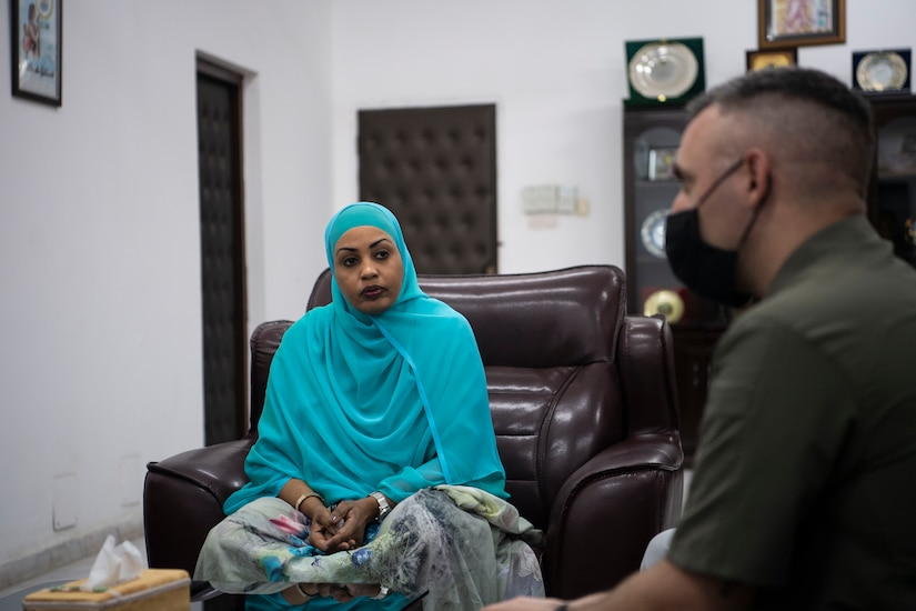 A man sits adjacent to a woman in a hijab.