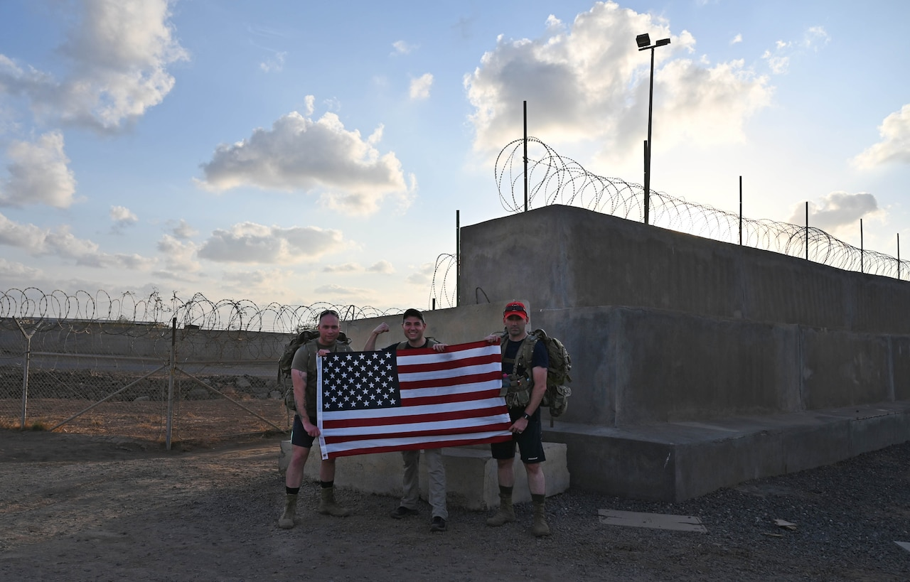 Three men holding a U.S. flag stand near barbed-wire fences.
