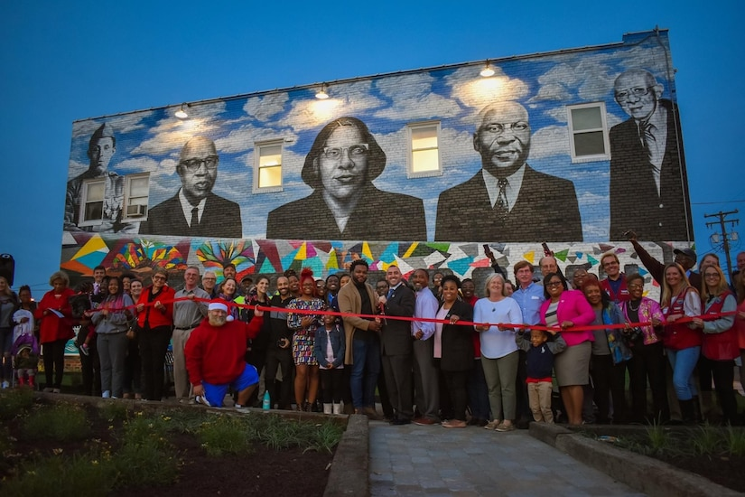 A crowd prepares to cut a ribbon in front of a mural on a building.