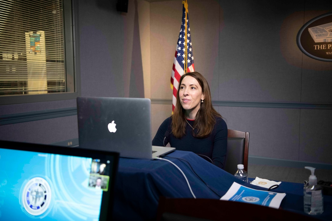 A woman seated at a computer speaks.