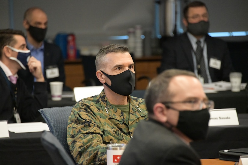 A man in uniform and wearing a mask observes a meeting.