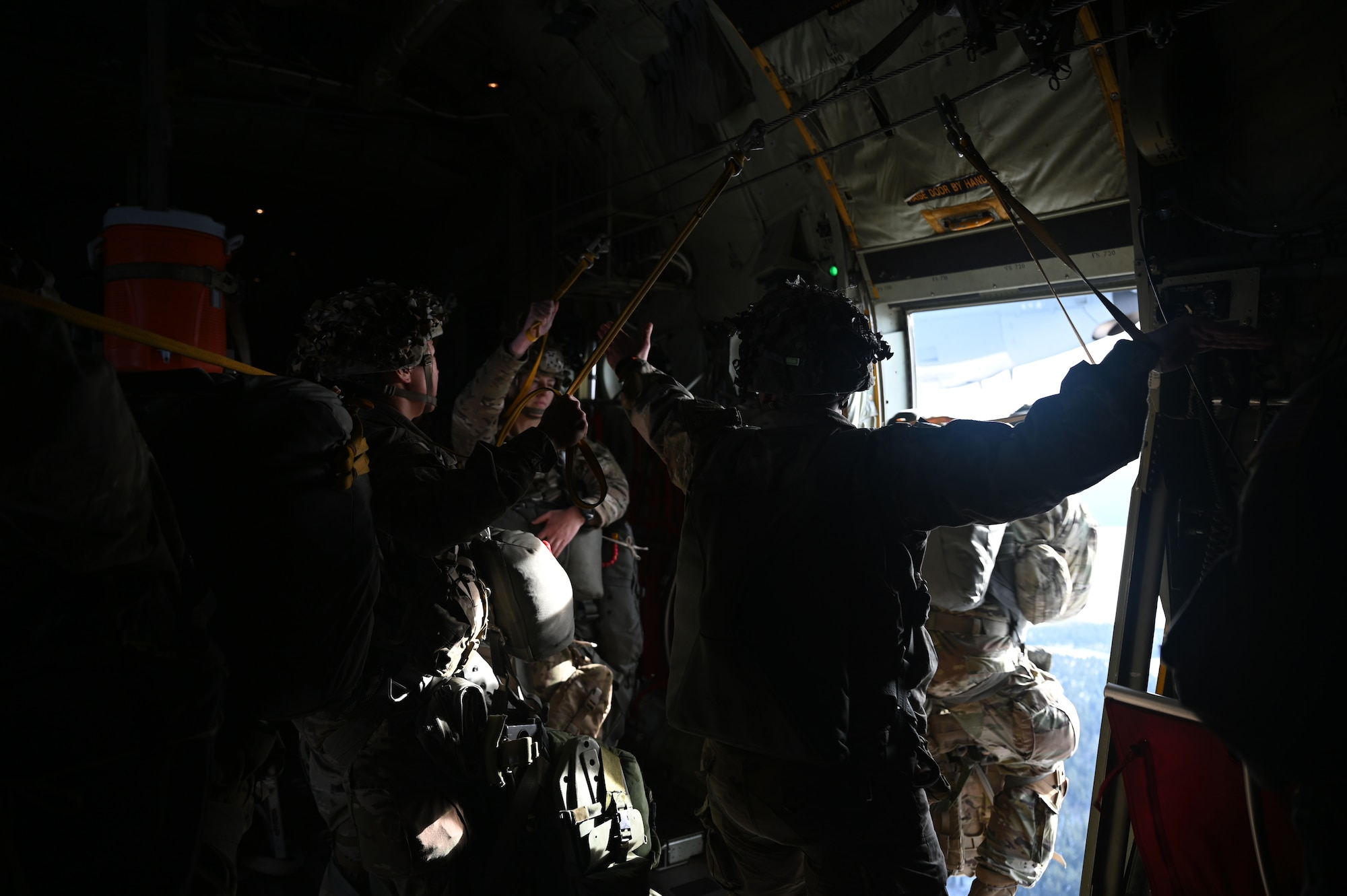 U.S. Army paratroopers assigned to the 1st Squadron (Airborne), 91st Cavalry Regiment, 173rd Airborne Brigade, assigned to Grafenwoehr Training Area, Germany, jump out of a U.S. Air Force C-130J Super Hercules aircraft.