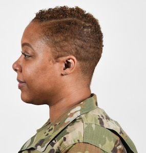 A female Soldier poses for an example photo with hair shorter than 1/4 inch, natural colored highlights, and earrings in the Army Combat Uniform, in support of an upcoming change in Army grooming and appearance standards.