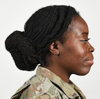 "A female Soldier poses for an example photo wearing ""locs"" and multiple hairstyles to illustrate an upcoming change to Army grooming and appearance standards. Soldiers will be authorized to wear multiple hairstyles if they can maintain a neat and professional appearance, and if the hairstyle doesn't impede the use of headgear or other equipment."