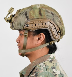 A female Soldier poses for an example photo with long hair while wearing tactical headgear to illustrate an upcoming change in Army grooming and appearance standards. The Soldier's hair is secured into a long ponytail and tucked underneath her Army Combat Uniform collar. Females with long hair will now have the option to wear a ponytail while wearing an Army Physical Fitness Uniform, conducting physical training in a utility uniform, or while wearing tactical headgear or other equipment.