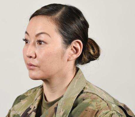 A female Soldier poses for an example photo with medium-length hair secured into a ponytail to support an upcoming change in Army grooming and appearance standards. Medium-length ponytails are only authorized for wear on the back of the scalp and cannot exceed the head's width or interfere with a Soldier's headgear.