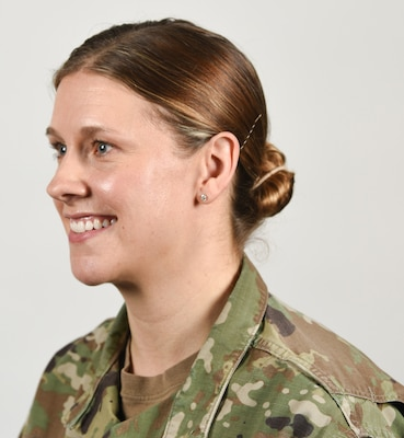 A female Soldier poses for an example photo with natural-colored highlights and wearing stud earrings in her Army Combat Uniform to illustrate an upcoming change to Army grooming and appearance standards. Female Soldiers will soon be authorized to wear earrings in their ACU if it meets the current size and dimensions standards. Individuals will not be allowed to wear earrings in a field environment or during a combat-related deployment, or in locations where access to regular hygiene is limited.