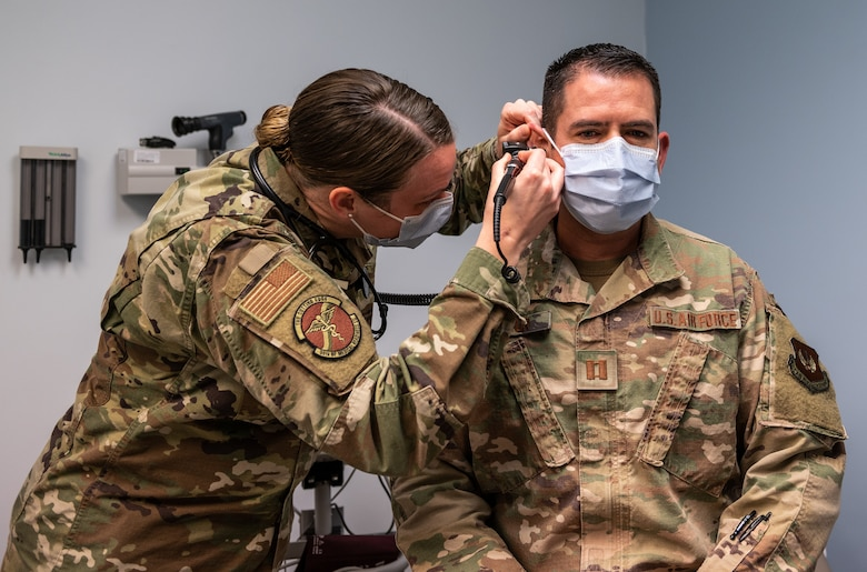 military medical physician inspect another member's ear
