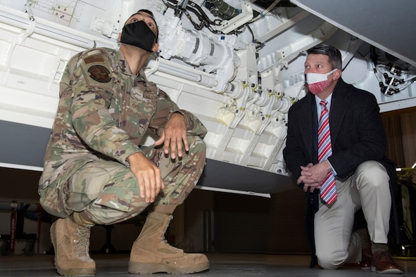 Staff Sgt. Christopher Lewis and Rep. Ronny Jackson look at an F-22 aircraft maintenance trainer