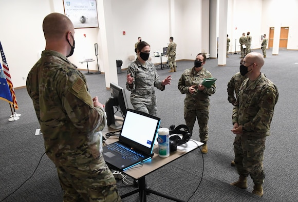 U.S. Air Force Master Sgt. Carolann Peteroli, 335th Training Squadron curriculum developer, explains the capabilities of the weather course virtual reality lab to Col. Chance Geray, 81st Training Group commander, during the 81st TRG Mock Tech Expo inside the Roberts Consolidated Aircraft Maintenance Facility at Keesler Air Force Base, Mississippi, Jan. 27, 2021. The 81st TRG level event was designed to prepare Keesler's nine innovation projects for the Air Education and Training Command level exposition. (U.S. Air Force photo by Kemberly Groue)