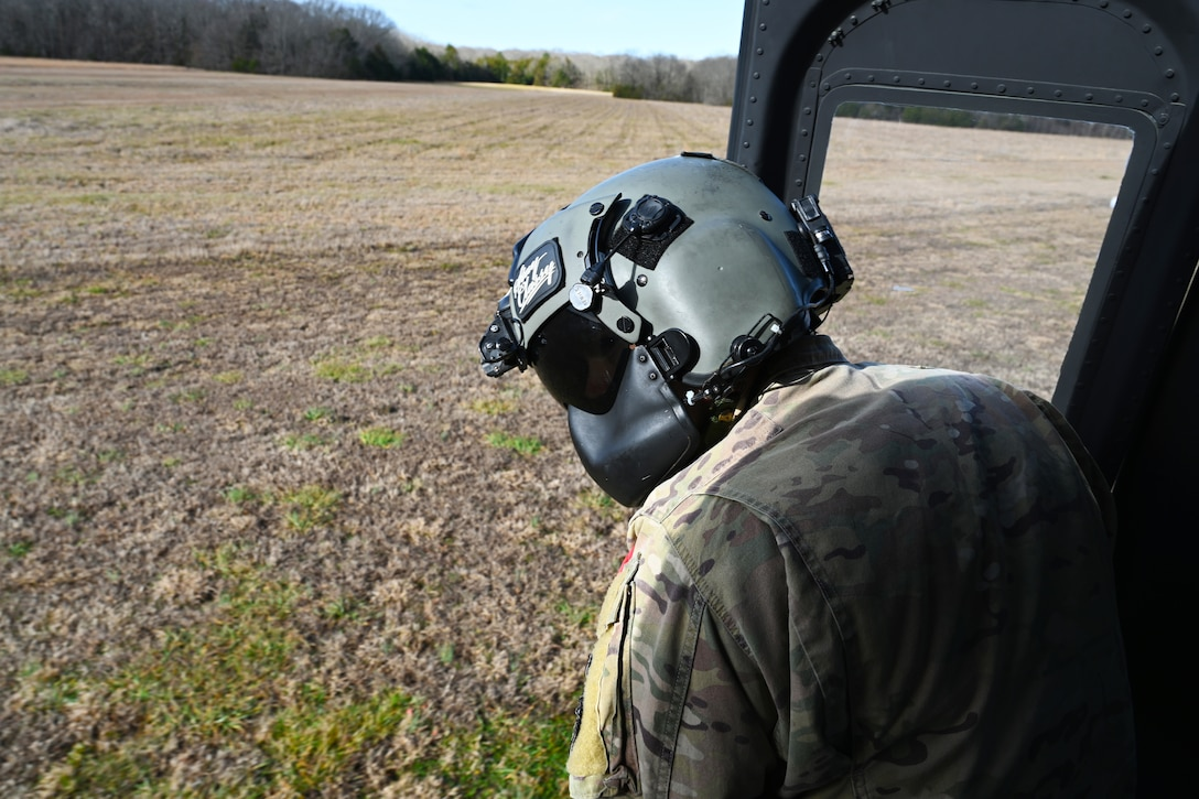 U.S. Air Force Tech. Sgt. Hayden Reynolds, 23rd Flying Training Squadron instructor flight engineer, checks the ground before landing a TH-1H Huey Jan. 26, 2021, in Columbus, Miss. The Vietnam-era UH-1H helicopters were converted into brand new TH-1H helicopters. (U.S. Air Force photo by Senior Airman Jake Jacobsen)