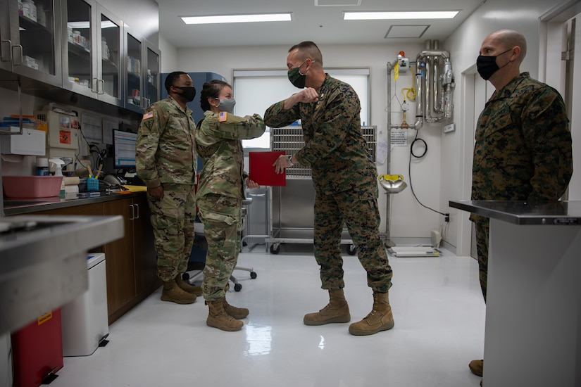 U.S. Marine Corps Col. Lance Lewis, center right, commanding officer of Marine Corps Air Station (MCAS) Iwakuni, hands an award to U.S. Army Capt. Austin Sorrels, center left, officer-in-charge of the Iwakuni Veterinary Treatment Facility (VTF) during a ceremony aboard MCAS Iwakuni, Jan. 7, 2021. The ceremony was held to present the VTF the Impact Iwakuni award for the impact they have made aboard the air station during the month of December. (U.S. Marine Corps photo by Lance Cpl. Triton Lai)