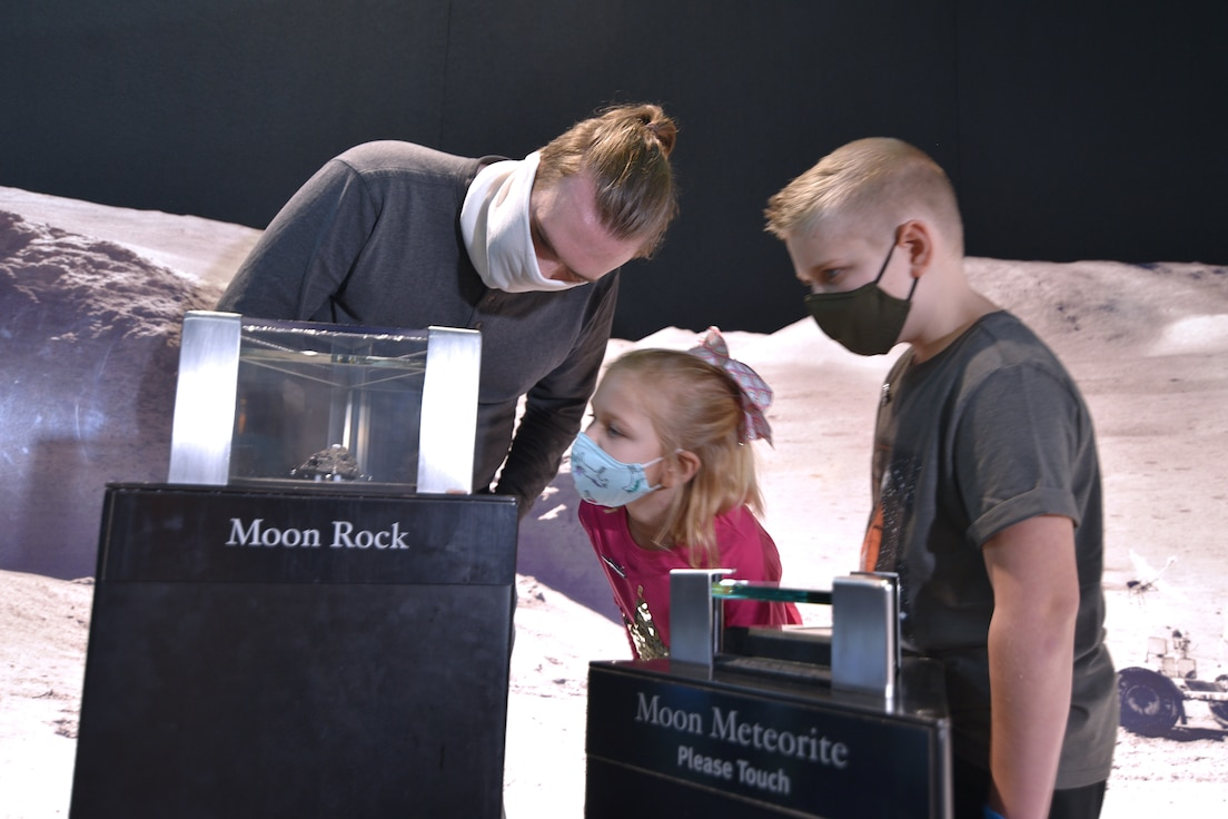 Visitors looking at a Moon Rock in the exhibit titled SPACE: A Journey to Our Future