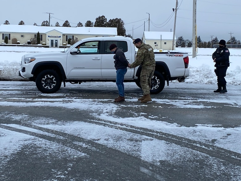 """Photo of the """"perpetrator"""", 102 IW Director of Inspections, Mr. Scott Etler, was hand-cuffed and both he and his vehicle were searched by Patrolman Staff Sgt. Erik Madden. Providing backup was Entry Controller Mr. Christopher Hankins."""