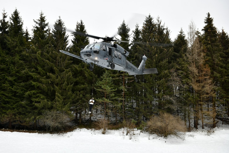 A U.S. Air Force HH-60G Pave Hawk from the 56th Rescue squadron hoists Capt. Bradley Beninati, 555th Fighter Squadron F-16 Fighting Falcon pilot, during combat survival training in the mountains near Pian Cansiglio, Italy, Jan. 21, 2021. All three 'survivors' made it to the designated area for recovery, where they were able to make contact with the 56th RQS for retrieval. (U.S. Air Force photo by Staff Sgt. K. Tucker Owen)