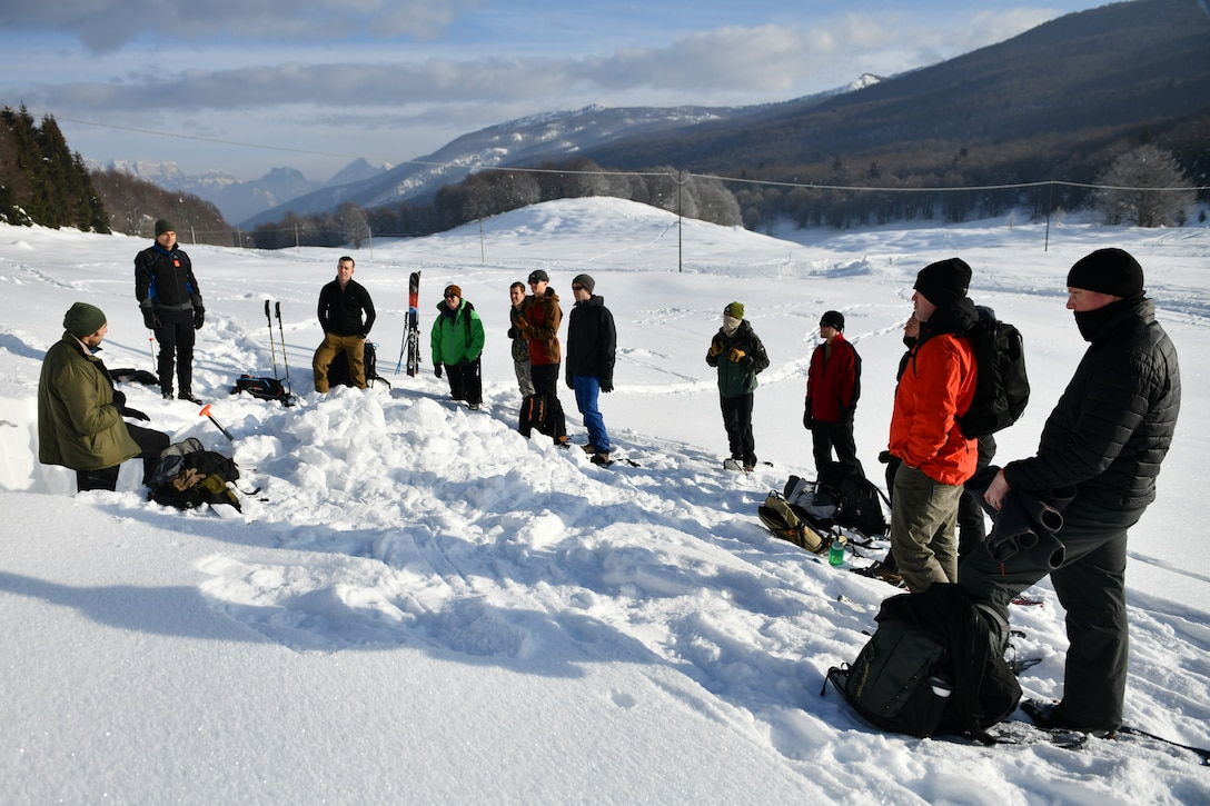 Italian air force Primo Luogotenente Stefano B., left, 15th Wing, 81st Search and Rescue Training Center instructor, speaks to U.S. Airmen assigned to the 31st Fighter Wing at Aviano Air Base, Italy, during an avalanche theory class at Piancavallo, Italy, Jan. 20, 2021. The class was attended by members of the 56th Rescue Squadron, and 510th and 555th Fighter Squadrons. (U.S. Air Force photo by Staff Sgt. K. Tucker Owen)