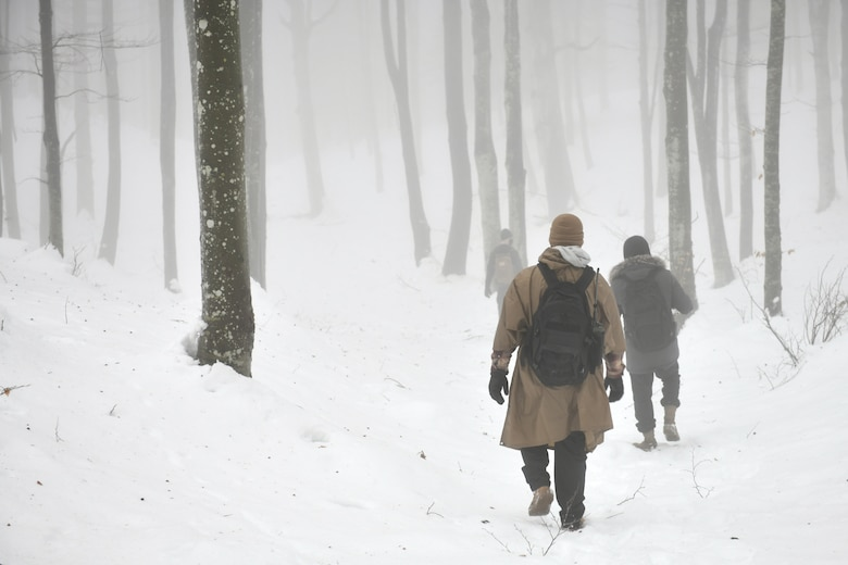 U.S. Air Force Airman 1st Class Jae Han, 31st Munitions Squadron precision guided missiles crew member, center, walks through the snow in the mountains near Pian Cansiglio, Italy, Jan. 21, 2021. Han was part of a four-man search team tasked with locating three simulated 'survivors' during a combat survival training exercise. (U.S. Air Force photo by Staff Sgt. K. Tucker Owen)