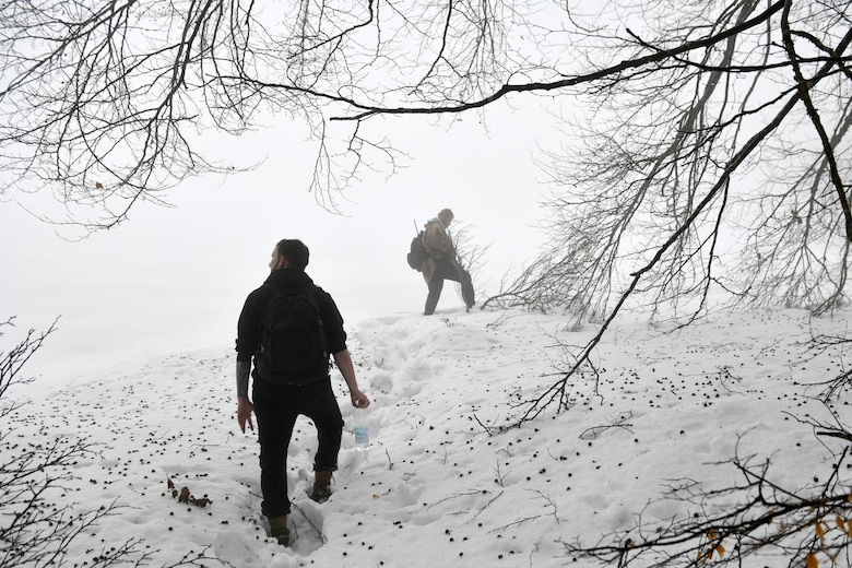 U.S. Air Force Senior Airman Niccolas Matranga, 31st Munitions Squadron munitions controller, left, and Airman 1st Class Jae Han, 31st Munitions Squadron precision guided missiles crew member, right, look for simulated 'survivors' during combat survival training in the mountains near Pian Cansiglio, Italy, Jan. 21, 2021. Matranga, Han and other Airmen participated in the exercise as the opposing forces, testing the survivors' ability to evade pursuit while awaiting recovery. (U.S. Air Force photo by Staff Sgt. K. Tucker Owen)
