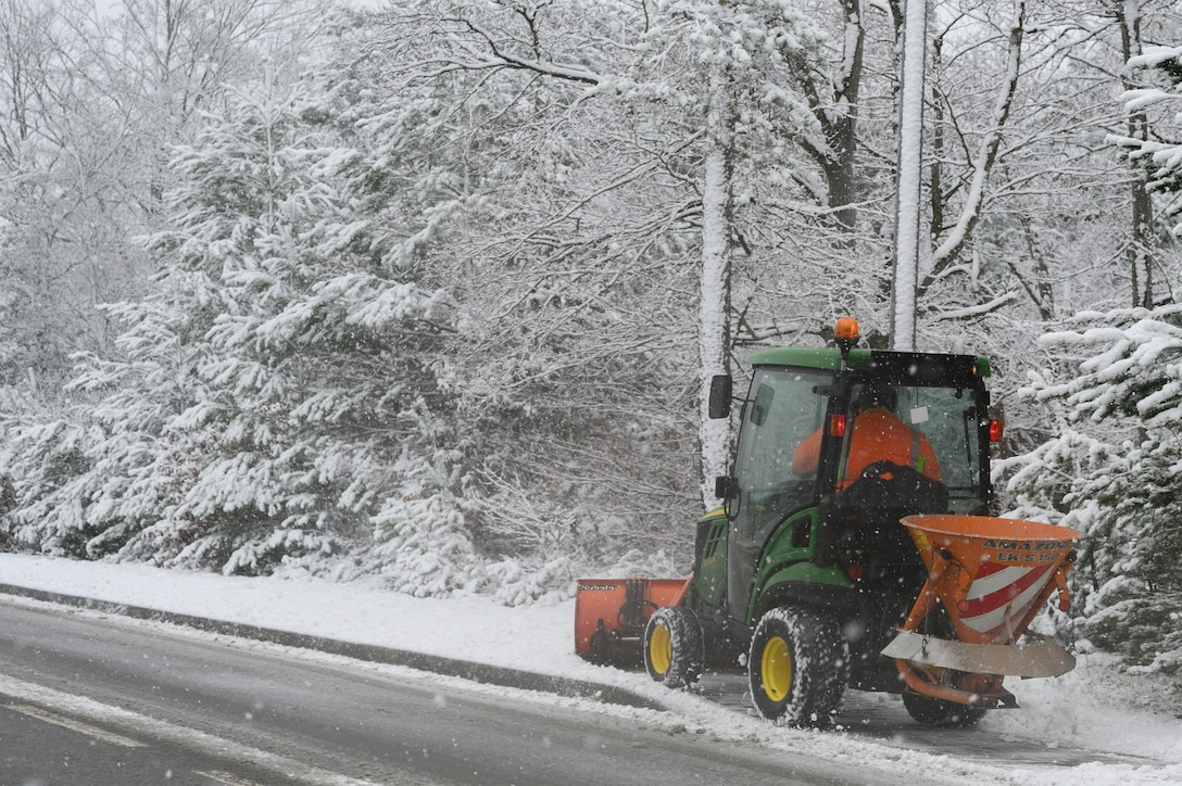 A snow tractor removes snow.