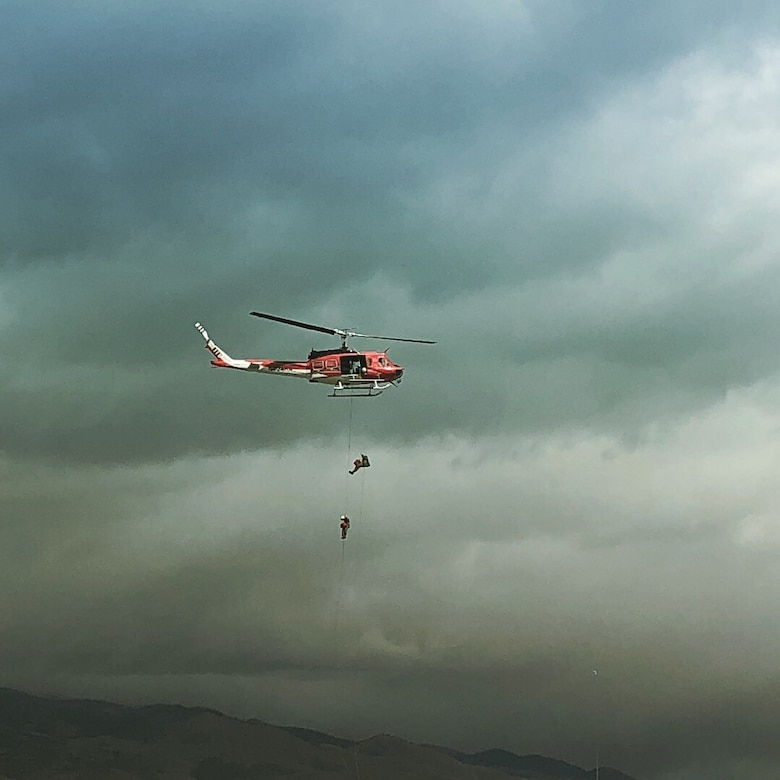 Helicopter rappellers train over a mountain