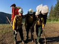 Three firefighters stand on a mountain