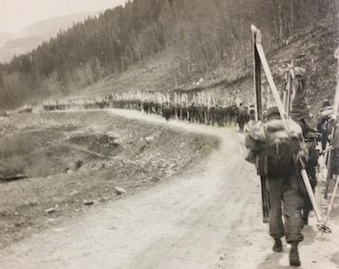 Soldiers march on a road carrying skis