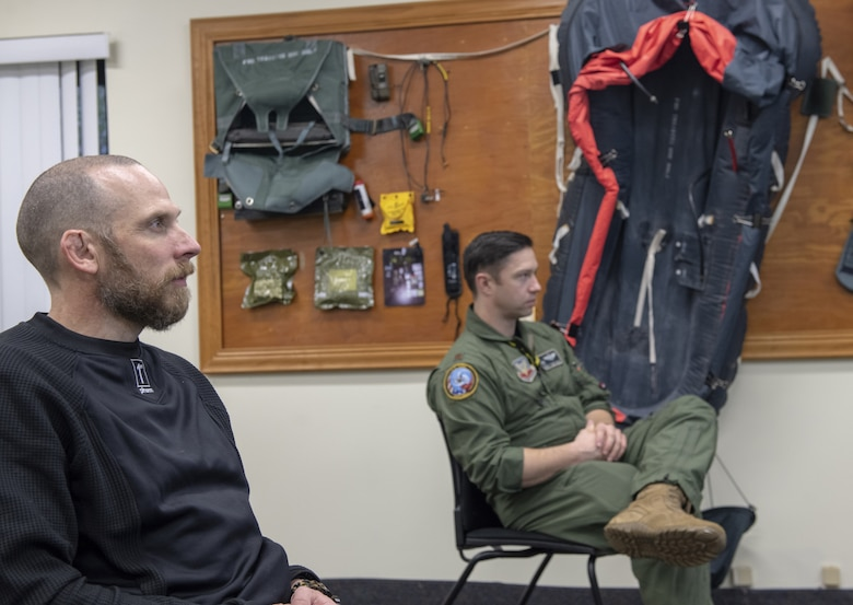 Photo of pilot and man listening to briefing.