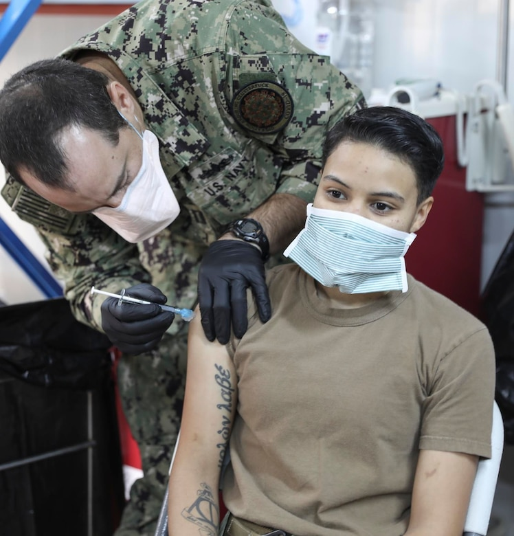 U.S. Navy Petty Officer 3rd Class Diana Elston, a surgical technician with the Navy's expeditionary medical unit, receives the COVID-19 vaccine at Erbil Air Base (EAB), Iraq on January 18, 2021. Combined Joint Task Force-Operation Inherent Resolve received 300 vaccines for the Combined Joint Operations Area, 110 of those were administered at EAB. At this time, like many locations, CJTF-OIR's supply of the vaccine is limited and will be administered to prioritized personnel. (U.S. Army National Guard photo by Staff Sgt. Noshoba Davis)