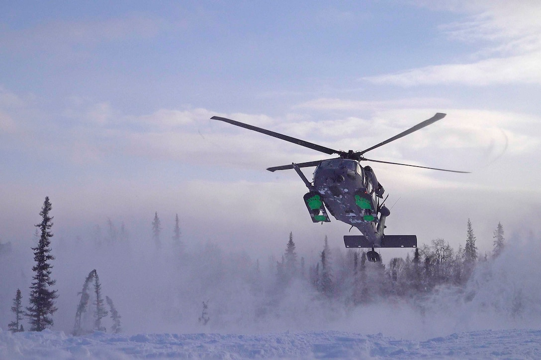 A helicopter prepares to land in the snow; trees seen in the background.